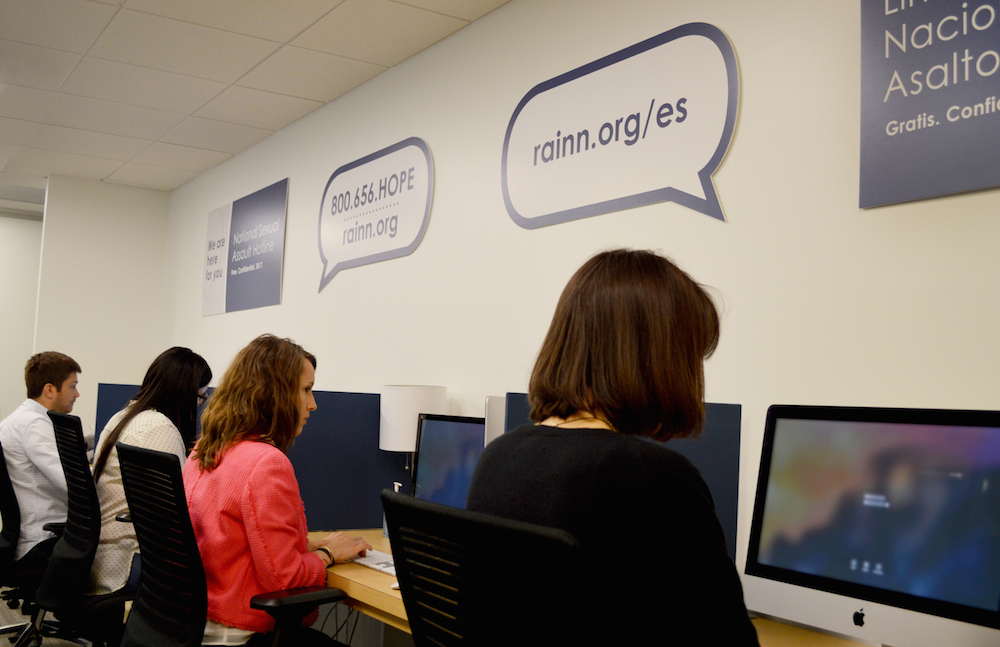 RAINN hotline support specialists sit at computers answering online hotline chats