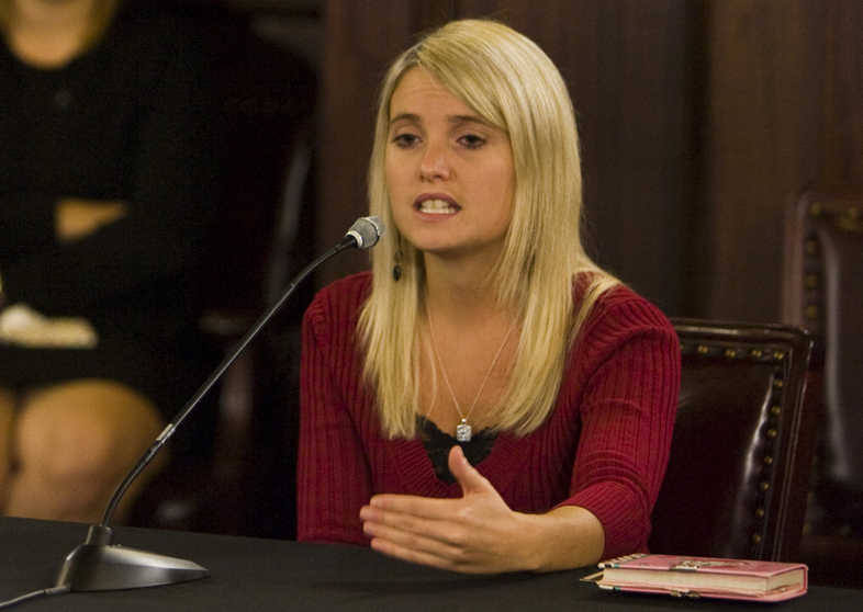 "Portrait of child sexual abuse survivor Erin Merryn of ""Erin's Law"" speaking into a microphone."