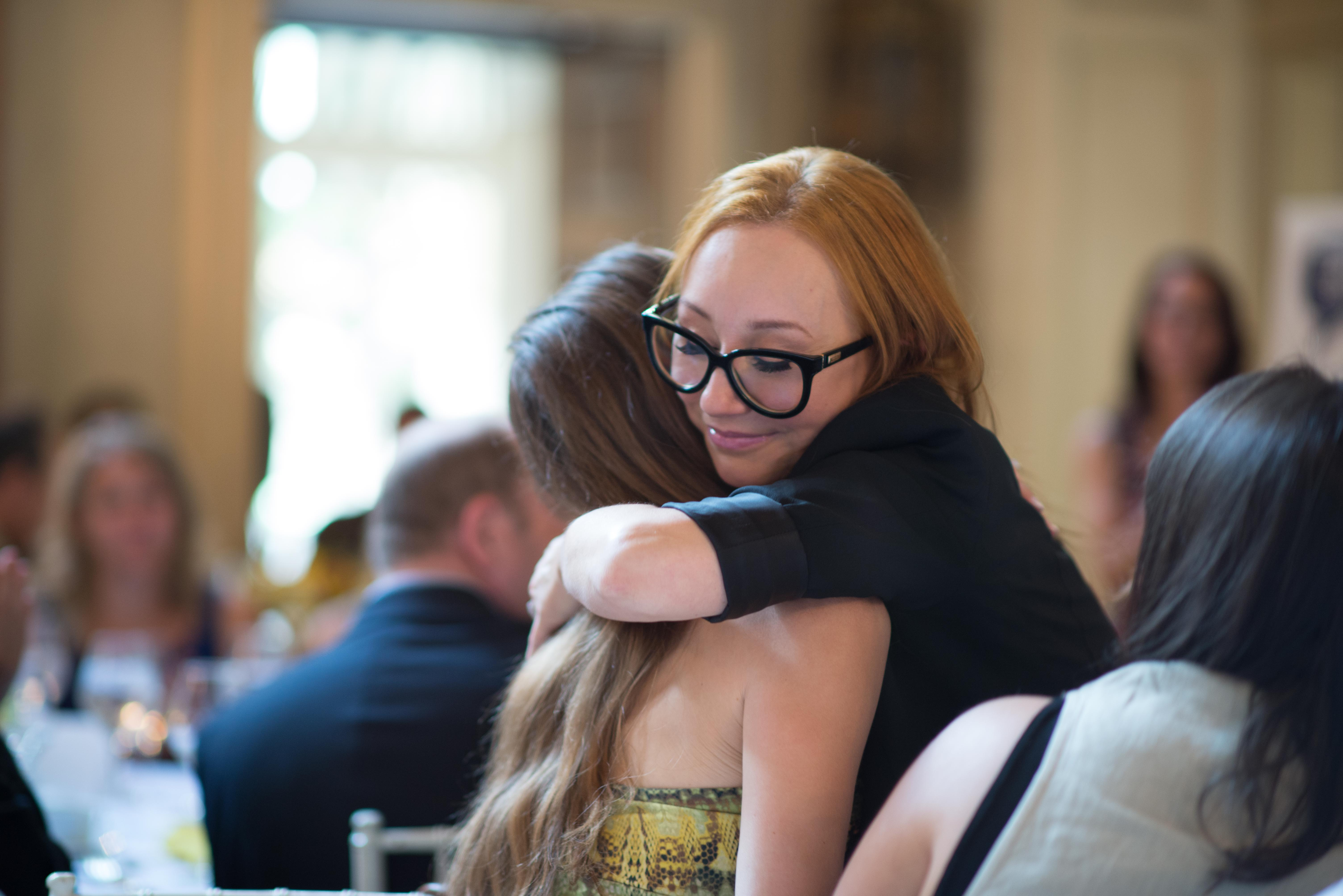 picture of Tori Amos as a spokesperson for the RAINN, hugging one of the audience members