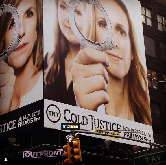 "Billboard saying ""TNT Cold Justice: Sex Crimes"" written beneath a portrait of two women holding handcuffs."