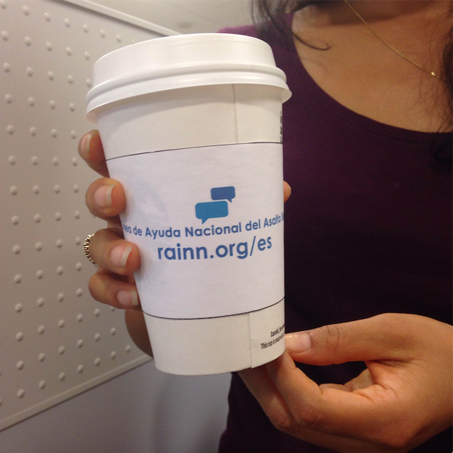 "Person holds a coffee cup with a sleeve. On the sleeve is written ""Linea de Ayuda Nacional del Asalto Sexual"" and ""rainn.org/es"""