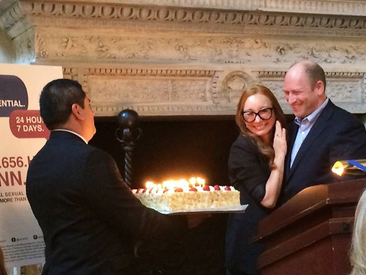 Singer Tori Amos hugs RAINN president Scott Berkowitz. A man presents her with a birthday cake.