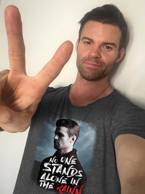 "Television actor Daniel Gillies portrait. He is wearing a special edition RAINN t-shirt. The t-shirt features Daniel's face and the words ""No one stands alone in the RAINN."" He holds up a peace sign to the camera."