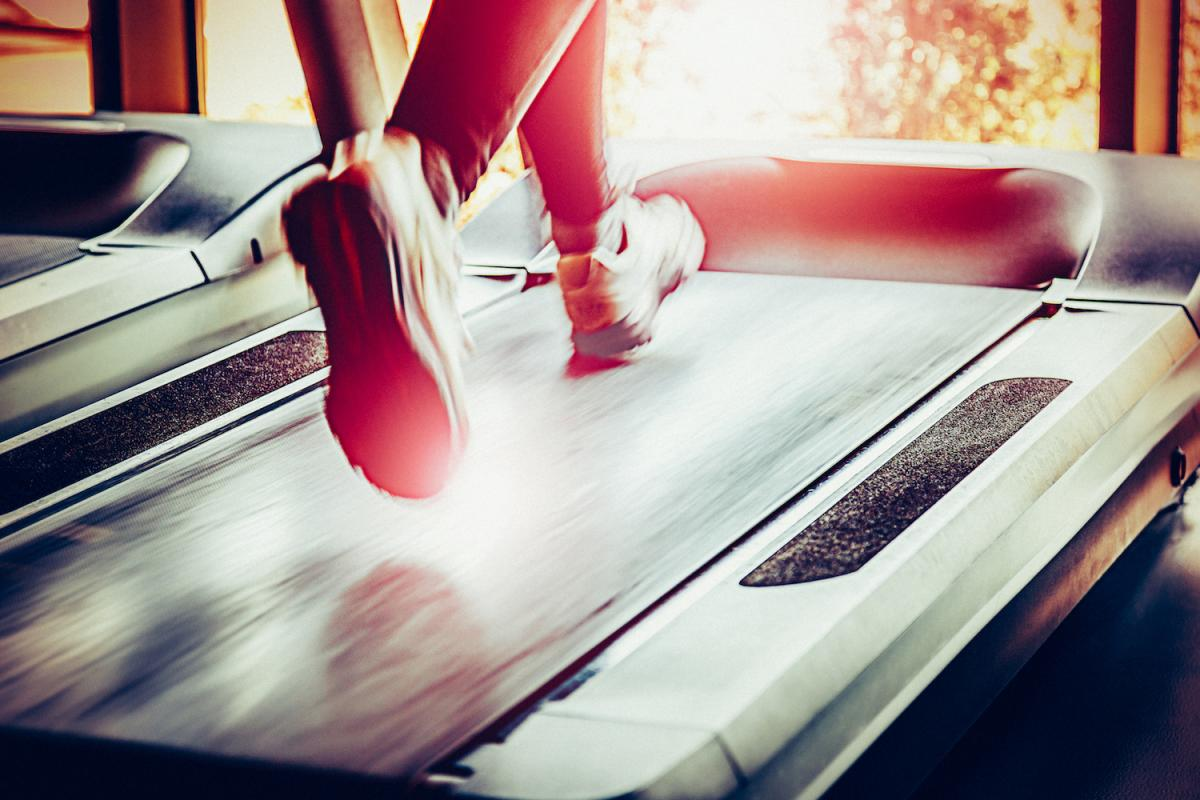 Feet shown running on treadmill, indoor gym
