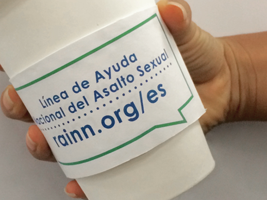 Spanish language coffee sleeves list the National Sexual Assault Hotline number