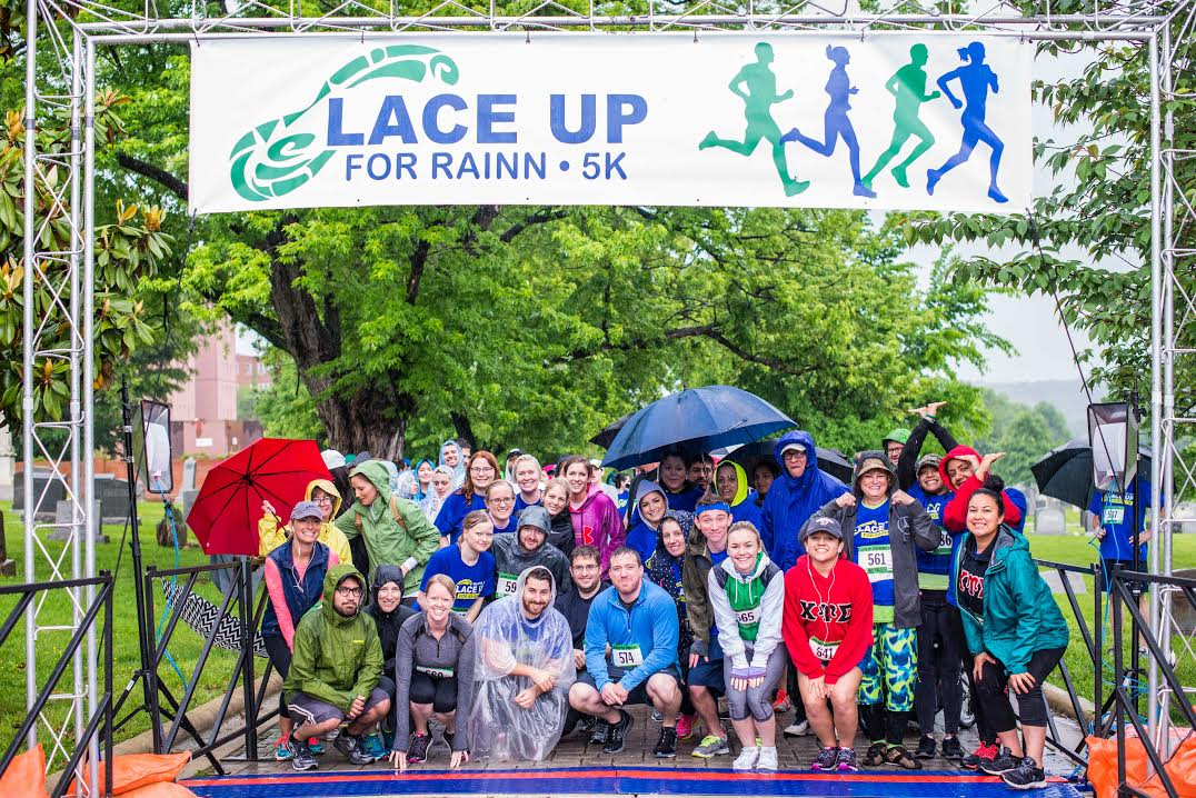 "Runners pose in the rain under a banner that reads ""Lace Up For RAINN 5k."" Part of a RAINN fundraising event."